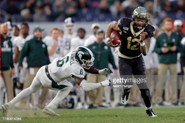 Quarterback Jamie Newman of the Wake Forest Demon Deacons rushes past safety David Dowell of the Michigan State Spartans during the first half of the...