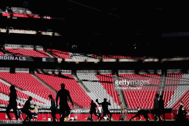 Quarterback Jared Goff of the Los Angeles Rams warms up with teammates before the NFL game against the Arizona Cardinals at State Farm Stadium on...