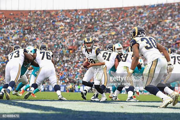 Quarterback Jared Goff of the Los Angeles Rams looks to hand off to teammate Todd Gurley during the first quarter of the game against the Miami...
