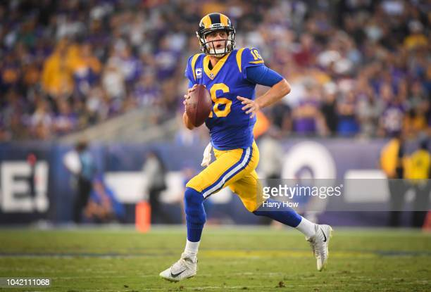 Quarterback Jared Goff of the Los Angeles Rams rolls out of the pocket to throw a touchdown pass to take a 21-17 lead in the second quarter against...