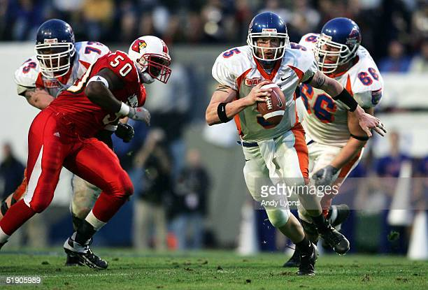 Quarterback Jared Zabransky of the Boise State Broncos runs with the ball against defensive lineman Chad Rimpsey of the Louisville Cardinals during...