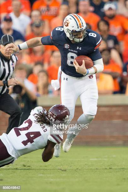 Quarterback Jarrett Stidham of the Auburn Tigers attempts to escape a tackle by defensive back Chris Rayford of the Mississippi State Bulldogs at...