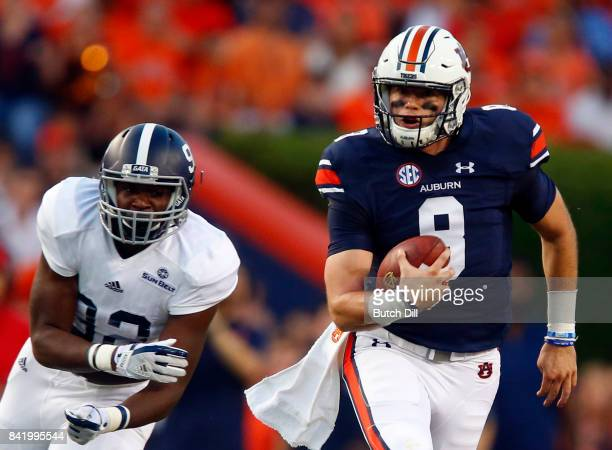 Quarterback Jarrett Stidham of the Auburn Tigers scrambles away from defensive end Raymond Johnson III of the Georgia Southern Eagles during the...