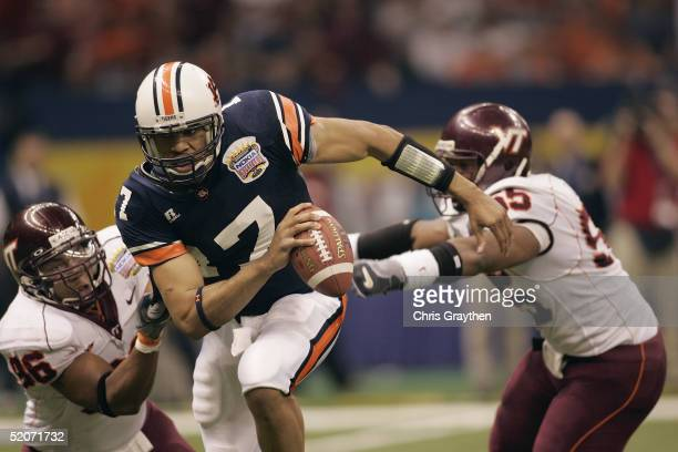 Quarterback Jason Campbell of the Auburn Tigers looks to pass while under pressure from linebacker Darryl Tapp and defensive end Noland Burchette of...
