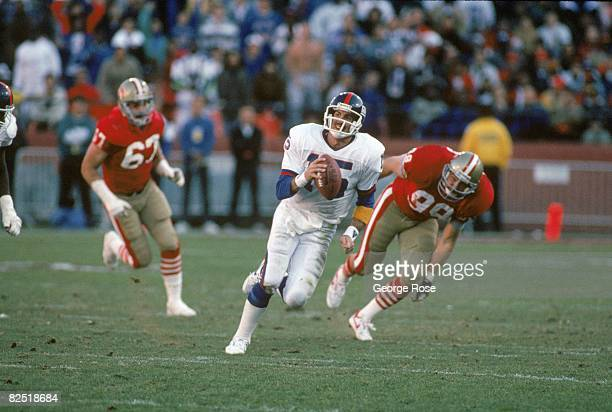 Quarterback Jeff Hostetler of the New York Giants runs with the ball away from San Francisco 49ers linebacker Mike Walter during the 1990 NFC...