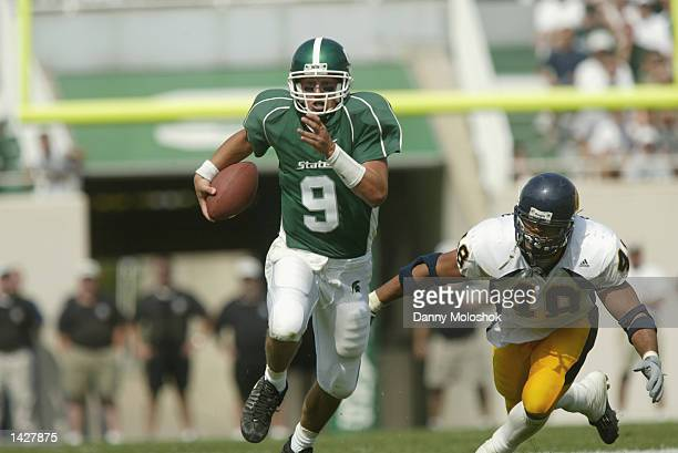 Quarterback Jeff Smoker of the Michigan State Spartans as defensive end Tully BantaCain of the California Golden Bears pursues him on September 14...