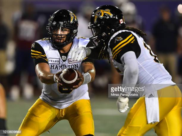 Quarterback Jeremiah Masoli of the Hamilton TigerCats prepares to hand over the ball to defensive back Alex Green against the Montreal Alouettes...
