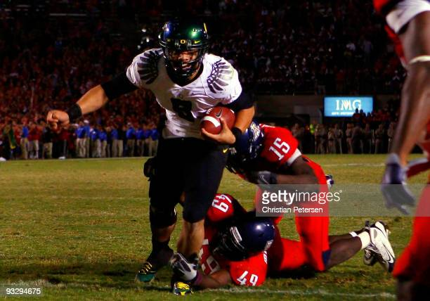 Quarterback Jeremiah Masoli of the Oregon Ducks rushes in the game winning touchdown in the second overtime past Earl Mitchell and Xavier Kelley of...
