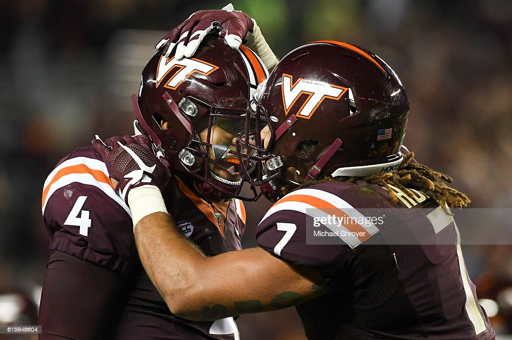 Quarterback Jerod Evans #4 of the Virginia Tech Hokies celebrates his touchdown throw with tight end Bucky Hodges #7 in the second half against the Miami Hurricanes at Lane Stadium on October 20, 2016 in Blacksburg, Virginia. Virginia Tech defeated Miami 37-16.