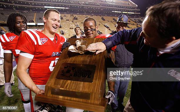 """Quarterback Jevan Snead, Patrick Trahan and head coach Houston Nutt of the Ole Miss Rebels celebrate with the """"Magnolia Bowl"""" trophy after defeating..."""
