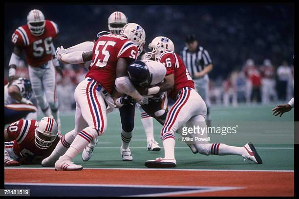 Quarterback Jim McMahon of the Chicago Bears runs for a touchdown as Don Blackmon and Raymond Clayborn of the New England Patriots try to hold him...