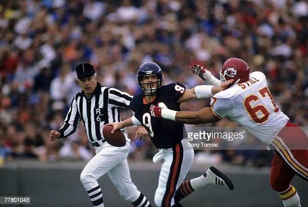 Quarterback Jim McMahon of the Chicago Bears throws a pass while being pursued by defensive lineman Art Still of the Kansas City Chiefs during a game...