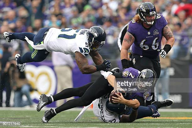Quarterback Jimmy Clausen of the Baltimore Ravens is tackled by defensive end Michael Bennett and outside linebacker Bruce Irvin of the Seattle...