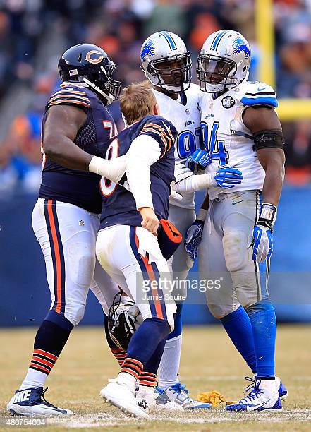 Quarterback Jimmy Clausen of the Chicago Bears is restrained by Michael Ola as he yells at Ezekiel Ansah and Jason Jones of the Detroit Lions after...