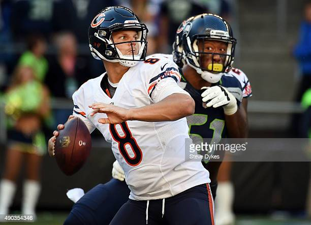 Quarterback Jimmy Clausen of the Chicago Bears passes the ball as outside linebacker Bruce Irvin of the Seattle Seahawks applies pressure during the...