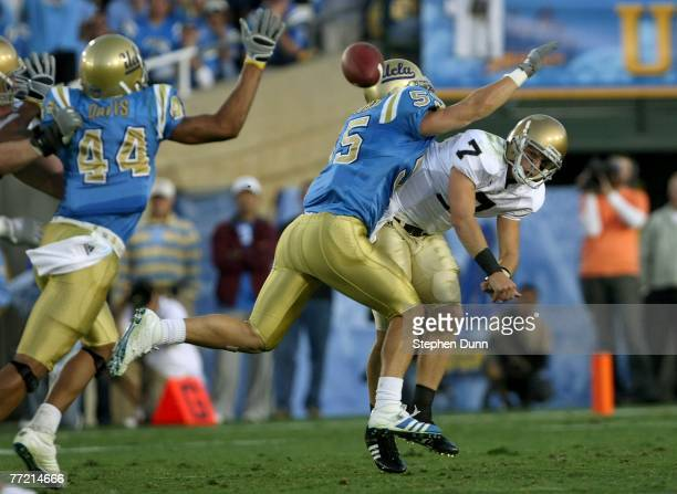 Quarterback Jimmy Clausen of the Notre Dame Fighting Irish is hit as he releases a pass by linebacker Korey Bosworth of the UCLA Bruins at the Rose...