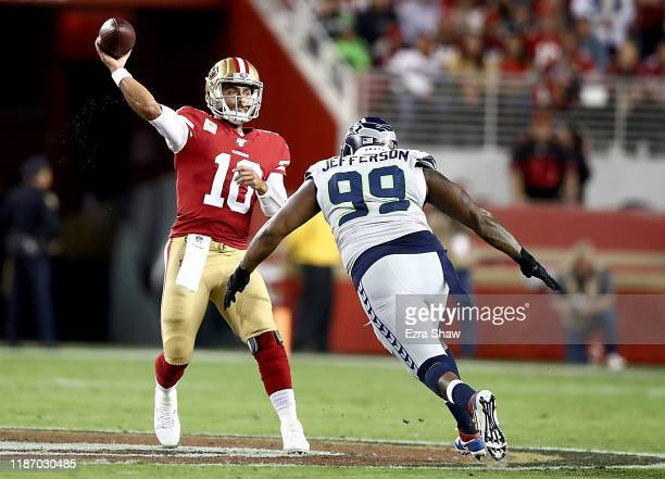Quarterback Jimmy Garoppolo of the San Francisco 49ers delivers a pass over the defense of defensive tackle Quinton Jefferson of the Seattle Seahawks...
