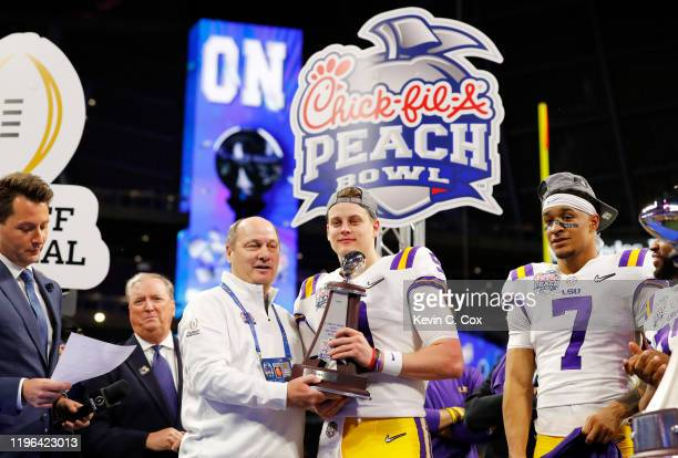 Quarterback Joe Burrow of the LSU Tigers receives the S. Truett Cathy Most Outstanding Player trophy after winning the Chick-fil-A Peach Bowl 28-63...