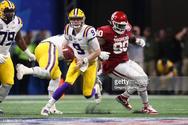 Quarterback Joe Burrow of the LSU Tigers scrambles against the defense of the Oklahoma Sooners during the Chick-fil-A Peach Bowl at Mercedes-Benz...
