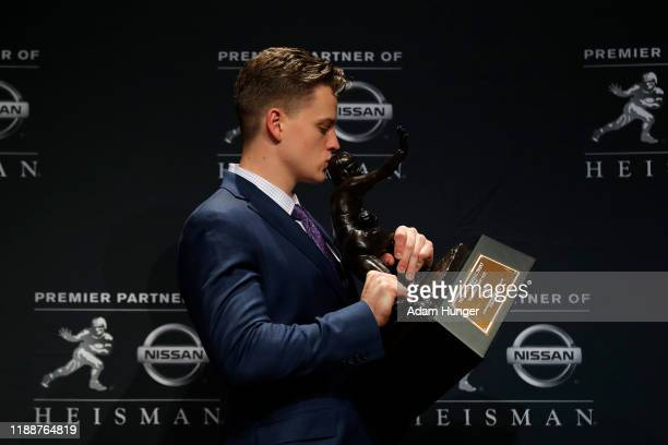 Quarterback Joe Burrow of the LSU Tigers winner of the 85th annual Heisman Memorial Trophy kisses the trophy on December 14 2019 at the Marriott...