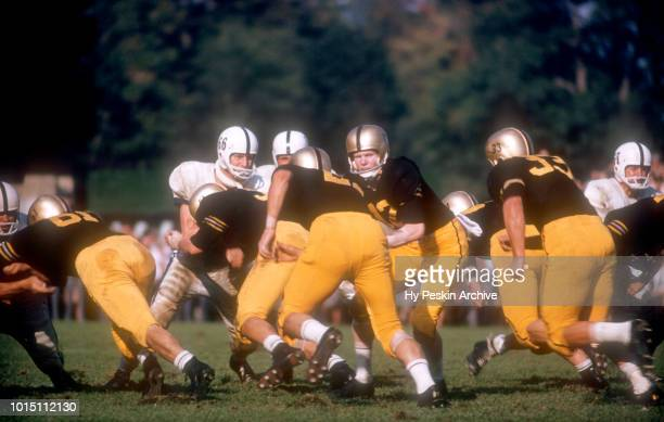 Quarterback Joe Caldwell of the Army Cadets hands the ball off to Harry Walters as Bob Anderson blocks during an NCAA game against the Penn State...
