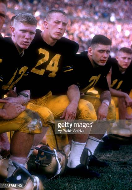 Quarterback Joe Caldwell Pete Dawkins and Bob Anderson of the Army Cadets kneel on the sidelines during an NCAA game against the Penn State Nittany...