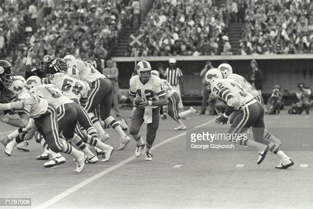 Quarterback Joe Ferguson of the Buffalo Bills turns to hand the ball off to running back O.J. Simpson during a game against the Pittsburgh Steelers...