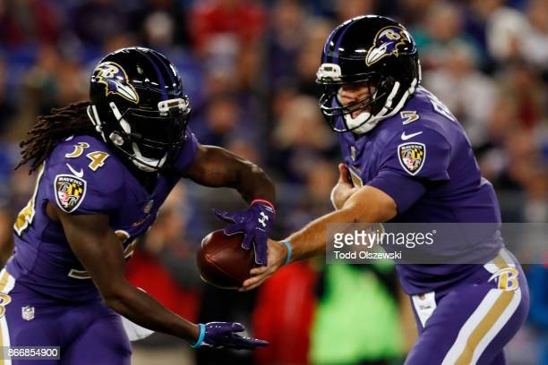 Quarterback Joe Flacco hands the ball of to running back Alex Collins of the Baltimore Ravens in the first quarter against the Miami Dolphins at MT...