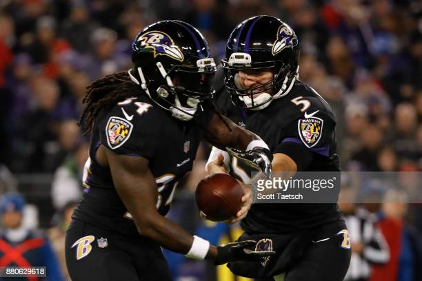 Quarterback Joe Flacco hands the ball off to running back Alex Collins of the Baltimore Ravens in the second quarter against the Houston Texans at MT...