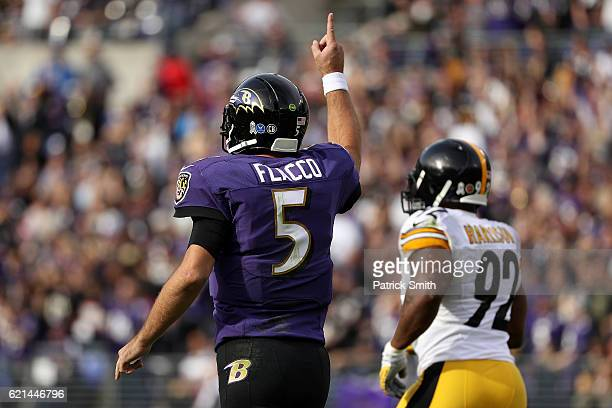 quarterback Joe Flacco of the Baltimore Ravens celebrates after throwing a first quarter touchdown pass to teammate wide receiver Mike Wallace...