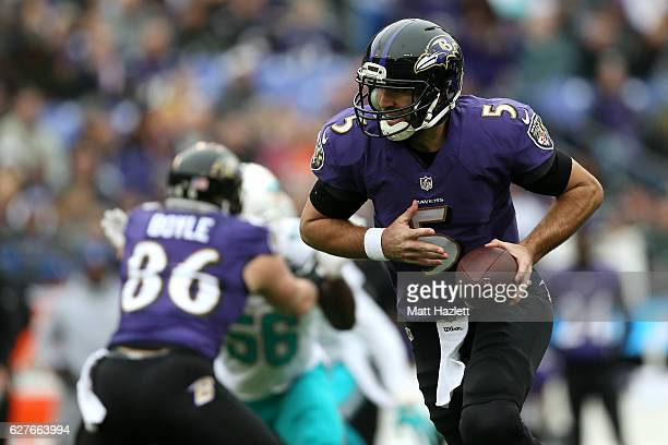 Quarterback Joe Flacco of the Baltimore Ravens drops back while teammate tight end Nick Boyle blocks against outside linebacker Donald Butler of the...