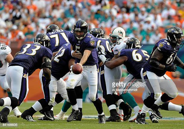 Quarterback Joe Flacco of the Baltimore Ravens hands off to running back Le'Ron McClain against the Miami Dolphins during their AFC Wild Card Game at...