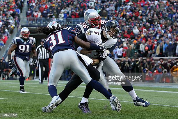 Quarterback Joe Flacco of the Baltimore Ravens is hit as he runs with the ball by Brandon Meriweather and Adalius Thomas of the New England Patriots...
