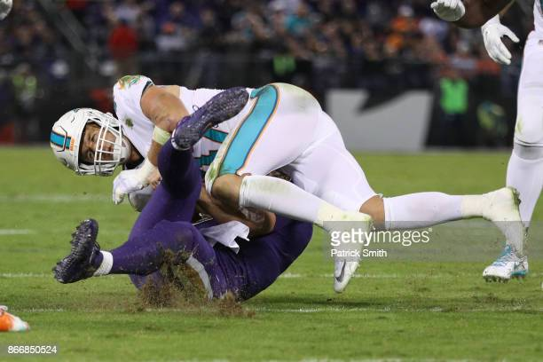 Quarterback Joe Flacco of the Baltimore Ravens is hit by middle linebacker Kiko Alonso of the Miami Dolphins as he slides in the second quarter...