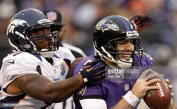 Quarterback Joe Flacco of the Baltimore Ravens is pressured by defensive end Robert Ayers of the Denver Broncos during the second half at M&T Bank...