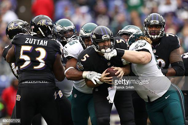Quarterback Joe Flacco of the Baltimore Ravens is sacked by defensive end Brandon Graham and defensive tackle Beau Allen of the Philadelphia Eagles...