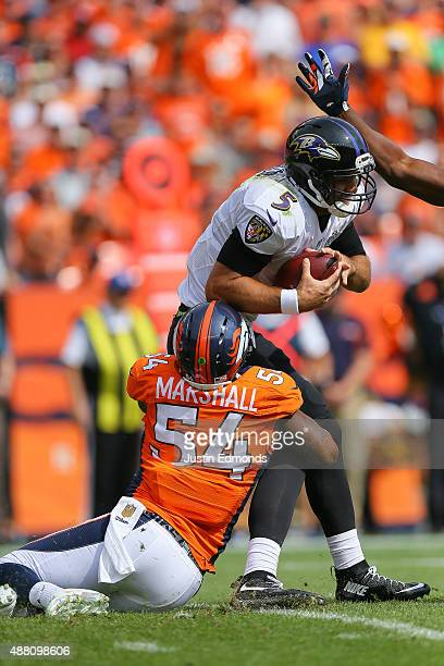 Quarterback Joe Flacco of the Baltimore Ravens is sacked by outside linebacker Brandon Marshall of the Denver Broncos in the first quarter of a game...