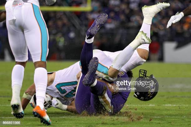 Quarterback Joe Flacco of the Baltimore Ravens is tackled by middle linebacker Kiko Alonso of the Miami Dolphins during the second quarter at MT Bank...