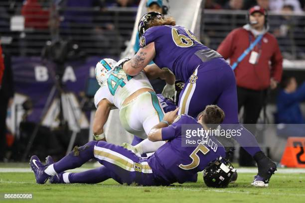 Quarterback Joe Flacco of the Baltimore Ravens lays on the filed after being hit by middle linebacker Kiko Alonso of the Miami Dolphins as he slides...