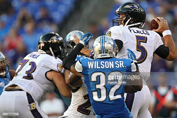 Quarterback Joe Flacco of the Baltimore Ravens looks to pass in front of defensive back Tavon Wilson of the Detroit Lions during the first half in...