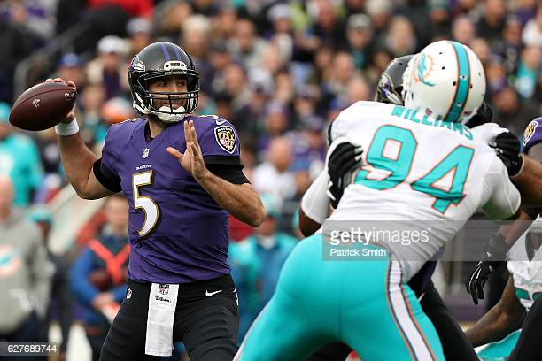 Quarterback Joe Flacco of the Baltimore Ravens passes the ball under pressure by defensive end Mario Williams of the Miami Dolphins in the second...