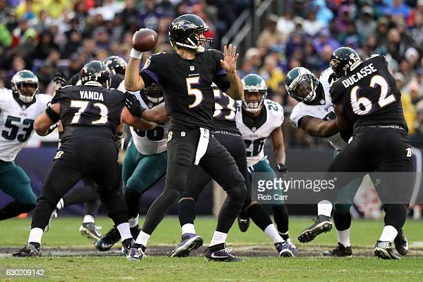Quarterback Joe Flacco of the Baltimore Ravens passes the ball while teammates guard Marshal Yanda and offensive guard Vladimir Ducasse block against...