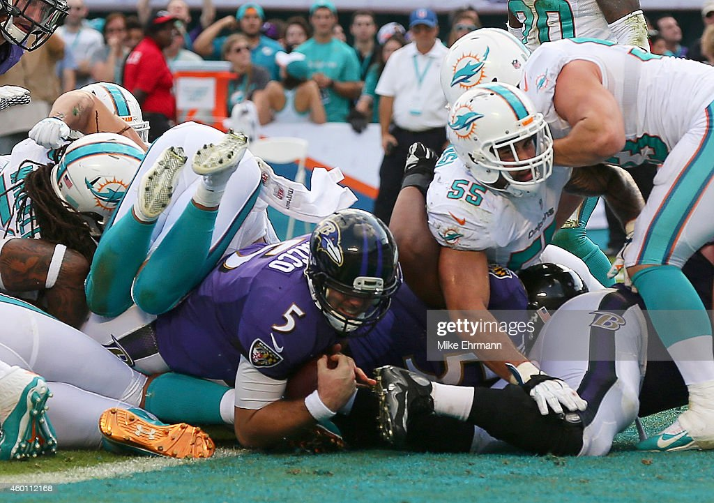 Quarterback Joe Flacco #5 of the Baltimore Ravens scores a fourth quarter touchdown against the Miami Dolphins during a game at Sun Life Stadium on December 7, 2014 in Miami Gardens, Florida.