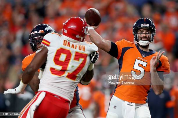 Quarterback Joe Flacco of the Denver Broncos delivers a pass over the defense of Alex Okafor of the Kansas City Chiefs in the game at Broncos Stadium...