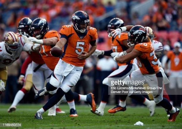 Quarterback Joe Flacco of the Denver Broncos does a fake handoff to running back Phillip Lindsay of the Denver Broncos during the first quarter of...