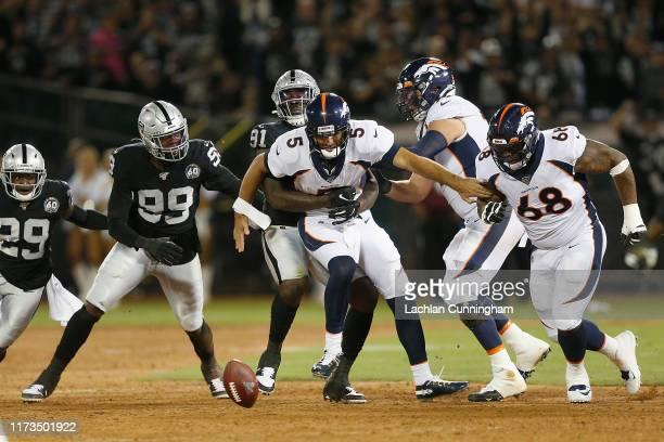 Quarterback Joe Flacco of the Denver Broncos is stripped of the ball by the Oakland Raiders defense in the second quarter of the game at RingCentral...