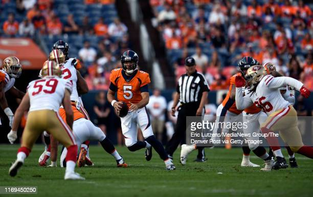 Quarterback Joe Flacco of the Denver Broncos looks for an opening while running the ball during the first quarter of the game on Monday August 19 at...