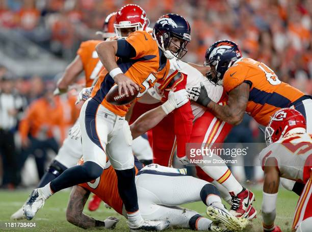 Quarterback Joe Flacco of the Denver Broncos scrambles against the defense of the Kansas City Chiefs in the game at Broncos Stadium at Mile High on...