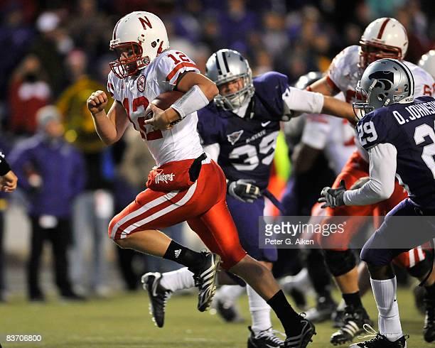 Quarterback Joe Ganz of the Nebraska Cornhuskers rushes past defensive back Otis Johnson and linebacker John Houlik of the Kansas State Wildcats...