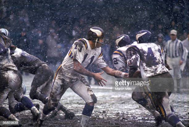 Quarterback Joe Kapp of the Minnesota Vikings hands of the ball to running back Dave Osborn as snow falls during a cold game against the Detroit...